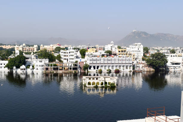 "Lake Pichola, Udaipur city, Indian state of Rajasthan, May 2019 ""u2013 Artificial fresh water lake, named after Picholi village. Two islands, Jag Niwas and Jag Mandir are located within Pichola Lake. Lake Pichola, Udaipur city, Indian state of Rajasthan, May 2019 ""u2013 Artificial fresh water lake, named after Picholi village. Two islands, Jag Niwas and Jag Mandir are located within Pichola Lake. lake palace stock pictures, royalty-free photos & images"