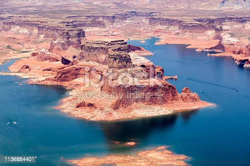 Lake Powell National Recreation Area with numerous bays, rock formations and motorboats on the water, aerial view, Utah, Arizona, USA.