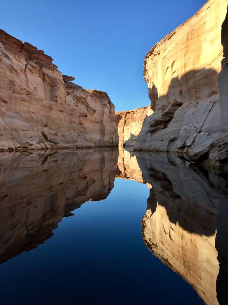 Lake Powell reflection Stand-up paddle boarding adventure before other boats arrive on Lake Powell. lake powell stock pictures, royalty-free photos & images