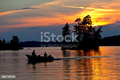 Fisherman fishing on a small boat at sunset over Burntside Lake, Ely Minnesota. Located in the Superior National Forest. Burntside Lake a popular tourist destination in the summer in Minnesota. Beautiful scenic area adjacent to the Boundary Water Canoe Area.