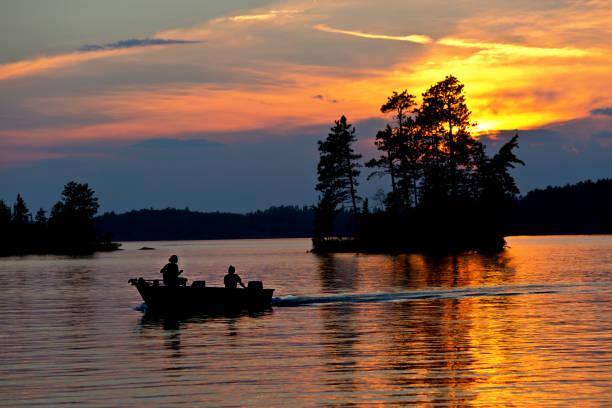 Lake Scene Fisherman Fishing at Ely, Boundary Water Canoe Area, Minnesota, USA at Sunset stock photo