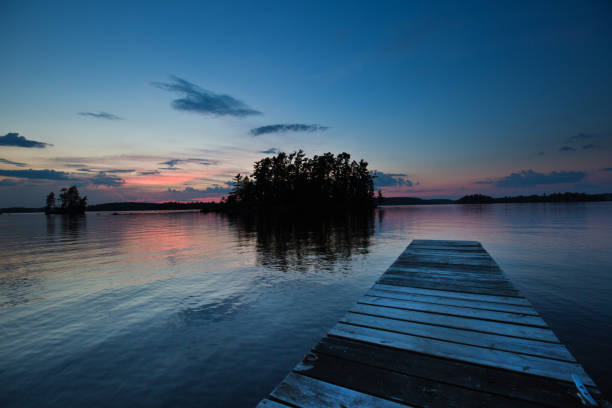 lake scene with boat dock at ely, boundary water canoe area, minnesota, usa at sunset - lakeshore stock photos and pictures