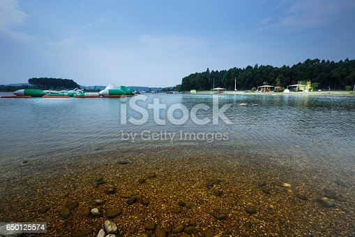 istock lake shore with pebbles and clear water 650125574