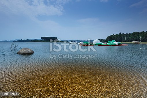 istock lake shore with pebbles and clear water 650125696