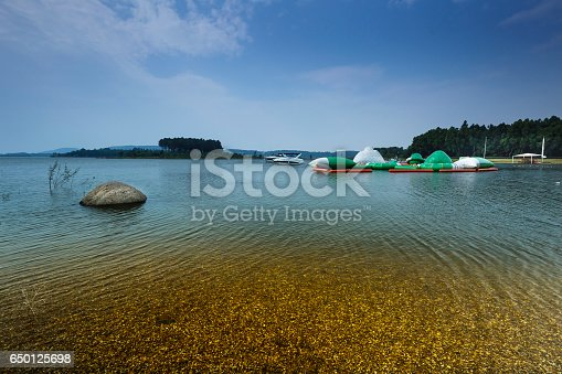 istock lake shore with pebbles and clear water 650125698