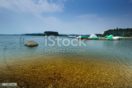 istock lake shore with pebbles and clear water 650125726