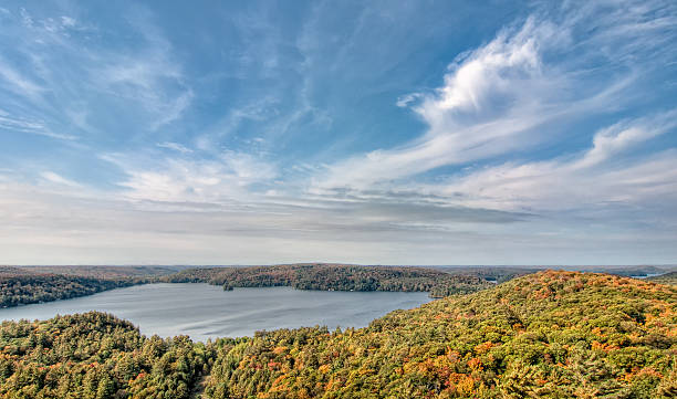 Lake Surrounded by Fall Trees and Whispy Clouds stock photo