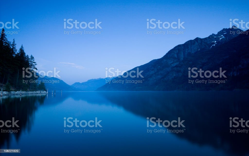 Lake Surrounded by Mountains and Forest at Dusk royalty-free stock photo