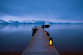 A weathered wooden pier extends out into the still blue evening waters of Lake Tahoe. Snow capped mountains and a stormy over cast sky reflect on the water.