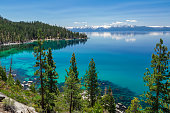 Picture of Lake Tahoe from east shore. There is a snow on the Sierra Nevada Mountains and some white clouds with reflection in turquoise waters of the lake.
