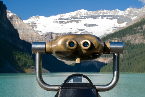Old fashioned coin operated binoculars pointed at Lake Louise.
