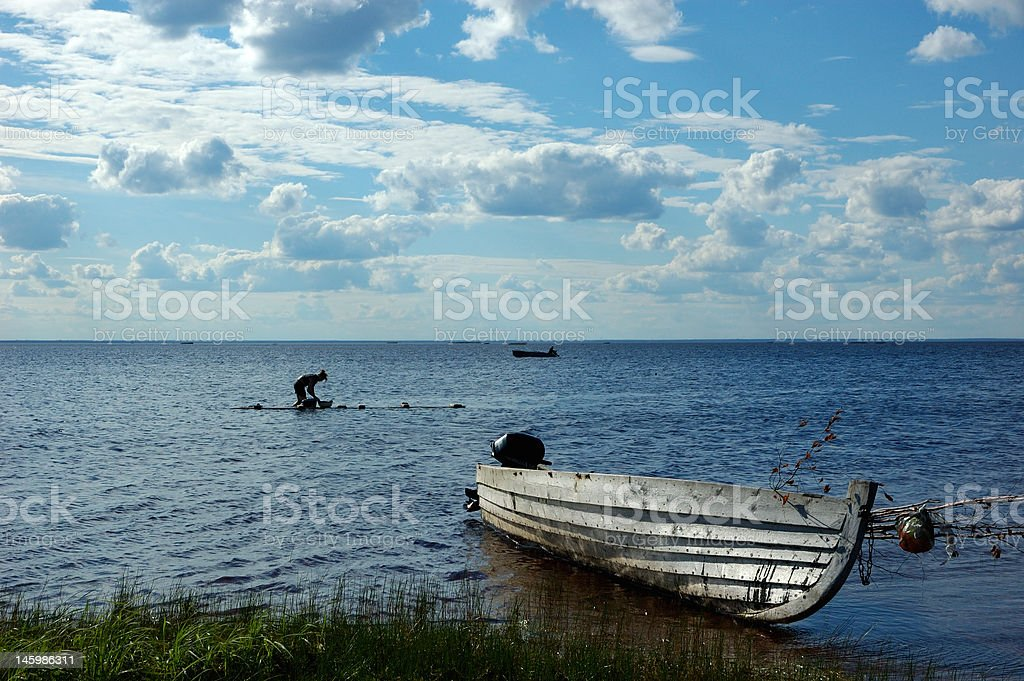 Lake view with old fishing boat and washing woman royalty-free stock photo