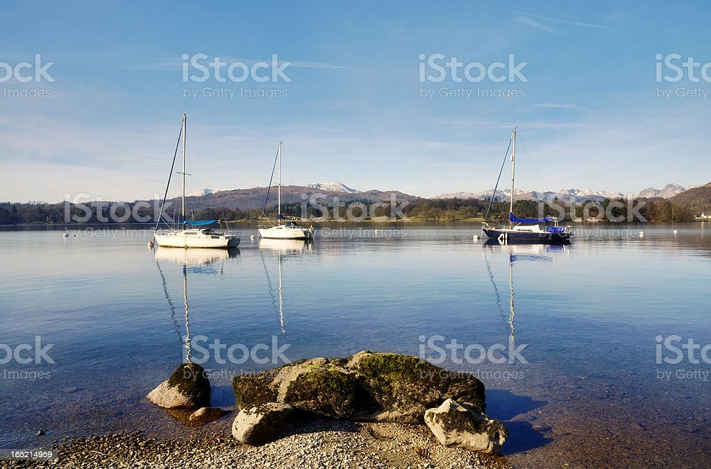 Lake Windermere with three boats and a rock stock photo