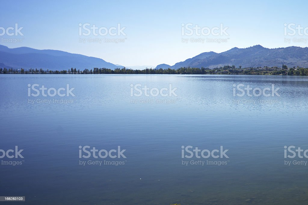Lake with blue mountains and sky. stock photo