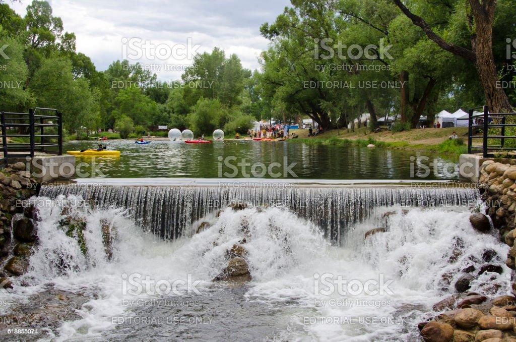 Lake With Kayaks Human Hamster Balls And A Waterfall Stock Photo