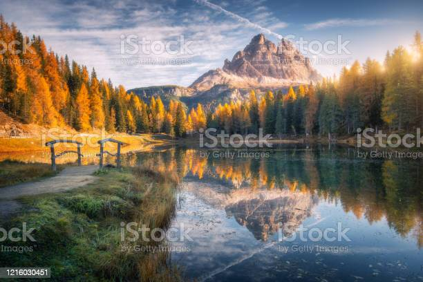 Photo of Lake with reflection in mountains at sunrise in autumn in Dolomites, Italy. Landscape with Antorno lake, small wooden bridge, trees with orange leaves, high rocks, blue sky in fall. Colorful forest