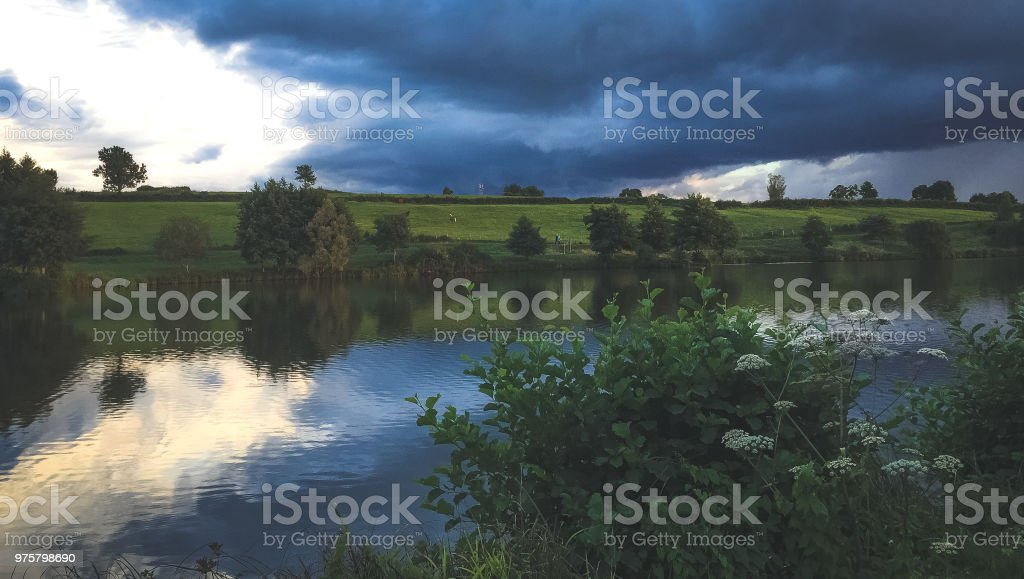 See mit Bäumen in den Sonnenuntergang - Lizenzfrei Anhöhe Stock-Foto