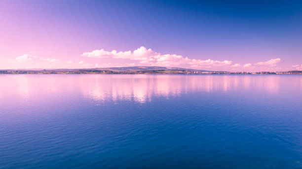 Lake Zug in central Switzerland. Clouds are reflected in water lake. Lake Zug in central Switzerland. Clouds are reflected in water lake. At the edge water is clear and see the bottom of the lake. zug stock pictures, royalty-free photos & images