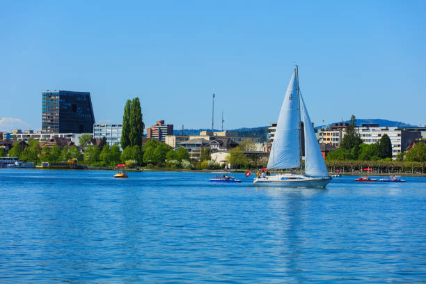 Lake Zug in Switzerland Zug, Switzerland - 6 May, 2016: people in boats on Lake Zug, buildings of the city of Zug in the background. Lake Zug is a lake in central Switzerland, situated between Lake Lucerne and Lake Zurich, the city of Zug is the capital of the Swiss canton of Zug. zug stock pictures, royalty-free photos & images