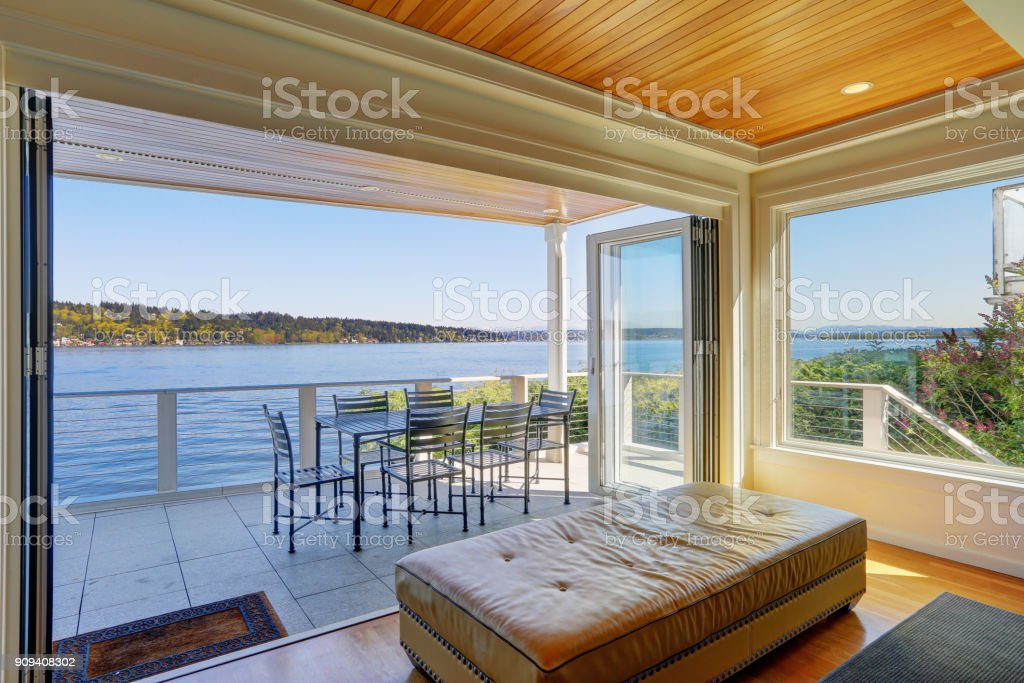 Waterfront home interior - a sliding glass wall opens to Large...