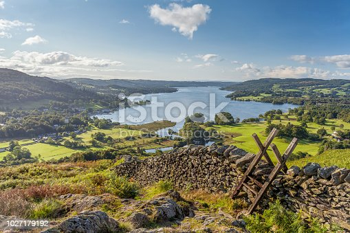 View of Windermere in the English Lake District taken from Loughrigg Fell. On a summer morning. With white fluffy clouds, shafts of Light on to Green fields with a Dry Stone Wall and wooden Style in the Foreground.