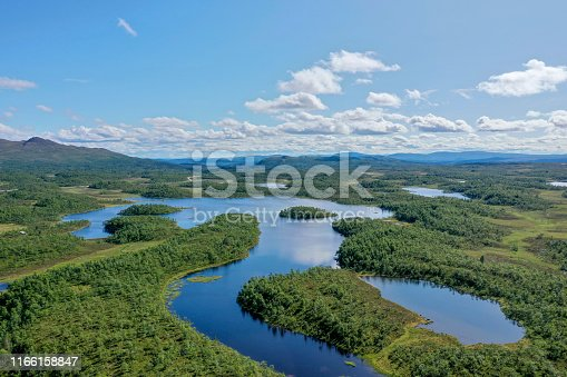 Multiple lakes and rivers seen in a huge green forest area in the summer.