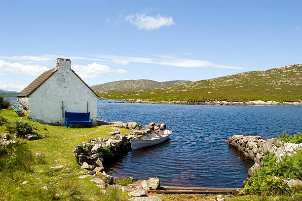 lakeside cottage and small boat in connemara, ireland - county clare stock pictures, royalty-free photos & images