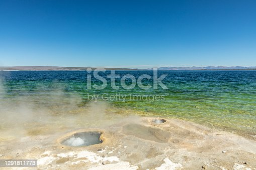 Steam rises from bubbling hot springs on the shore of Yellowstone Lake.