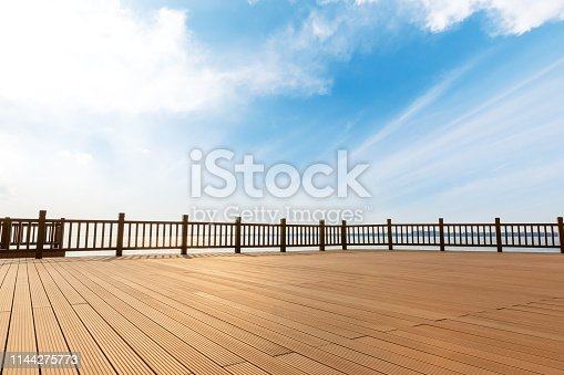 Lakeside wood floor platform and blue sky with white clouds landscape