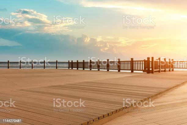 Photo of Lakeside wood floor platform and sky clouds at sunset