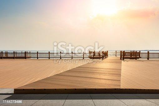 Lakeside wood floor platform and sky clouds landscape at sunset