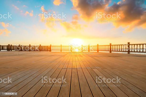 Photo of Lakeside wood floor platform and sky clouds at sunset.