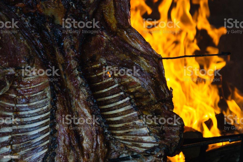 Un cordero se 'al asador' sobre un fuego de leña en la Patagonia Argentina - foto de stock