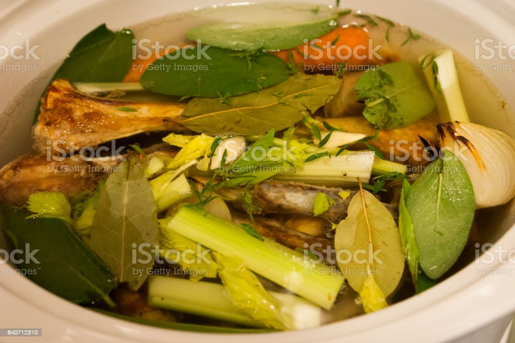 lamb bones, carrots, roasted onions, sage, bay leaves, garlic cloves and celery simmering in a crock pot to cook down into a bone broth for good health stock photo