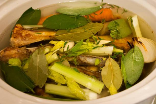 Lamm Knochen, Karotten, Röstzwiebeln, Salbei, Lorbeer, Knoblauchzehen und Sellerie in einem Topftopf simmering nach unten in einen Knochen Brühe für eine gute Gesundheit zu kochen – Foto