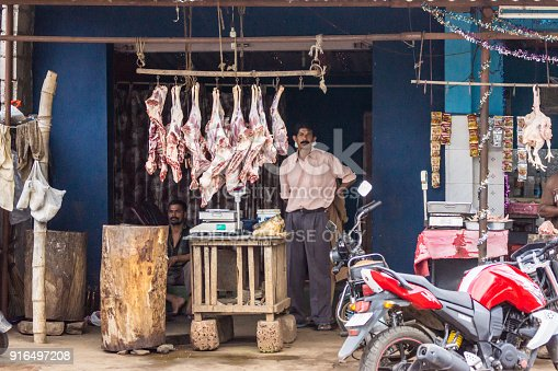 Coorg, India - October 29, 2013: Along street butcher shop with two butchers cutting sheep meat, mutton. Killed lamb quarters on hooks. Motorbikes.