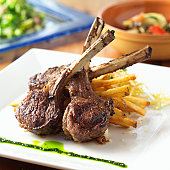 Lollipop lamb chops on a bed of french fries with salad in background, shot with shallow focus.