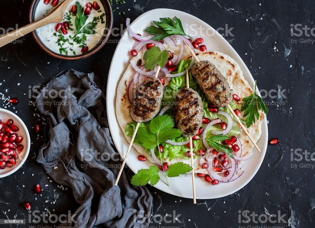 Lamb kebab on flatbread with lettuce, onions and pomegranate stock photo