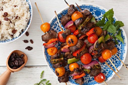 An overhead close up shot of several lamb kabobs on a plate and a bowl of rice with raisins.