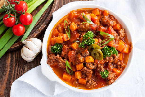 Lamb sweet potato chili Lamb sweet potato chili with fresh herbs and tomatoes, onion, garlic on wooden table stew stock pictures, royalty-free photos & images