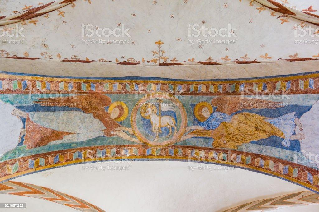 Cordeiro com uma cruz e bandeira, cordeiro de Deus e dois anjos, uma pintura românica - foto de acervo