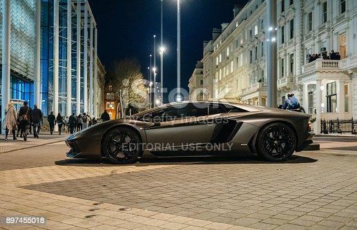 London: Rich businessmen party on the balcony with unique luxury super-car parked on Exhibition Rd, Kensington London. Lamborghini Aventador is a mid-engine sports car