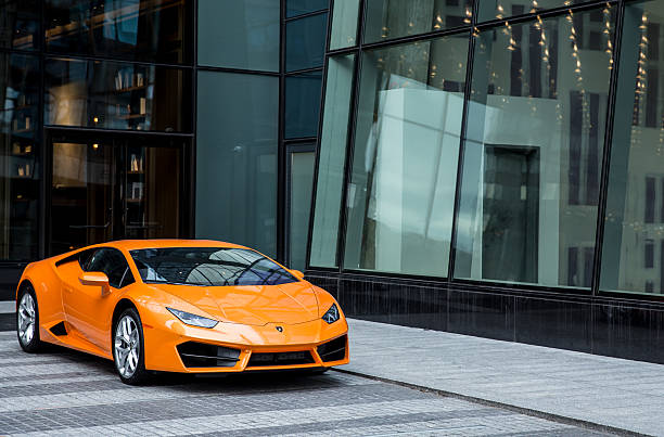 Lamborghini Huracan car of orange color New York, United States - December 29, 2016: Lamborghini Huracan car of orange color, parked near a hotel in Manhattan sports car stock pictures, royalty-free photos & images