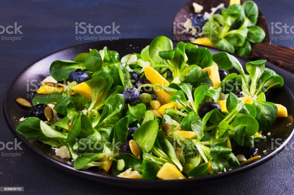 Lamb's lettuce, mango, blueberries and cheese salad on black plate stock photo