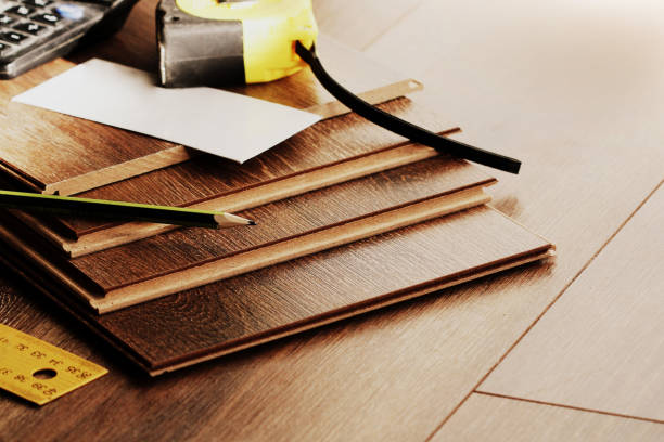 Laminate floor planks and tools on wooden background stock photo