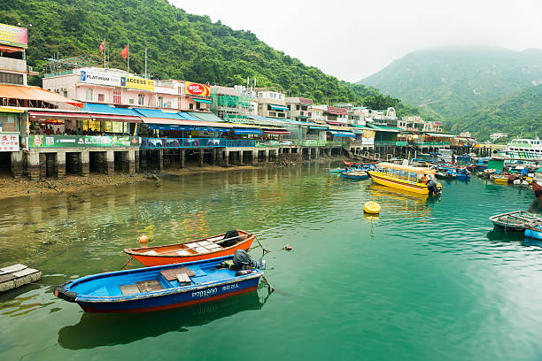 Lamma Island Scenic Harbor Boats in Sok Kwu Wan Village This is a horizontal, color photograph of the scenic harbor and village in Sok Kwu Wan Village on Lamma Island in Hong Kong. Colorful boats float on the water and green mountains disappear into the fog in the background. new territories stock pictures, royalty-free photos & images