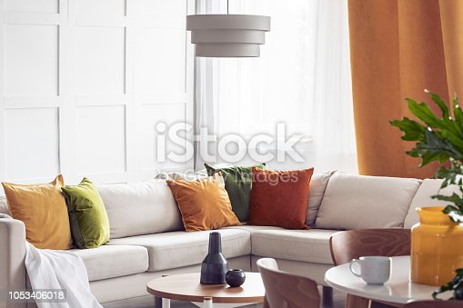 Lamp above table in bright living room interior with yellow pillows on white corner sofa. Real photo