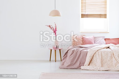 istock Lamp above table with flowers in pink pastel bedroom interior with window above bed. Real photo 1004109226