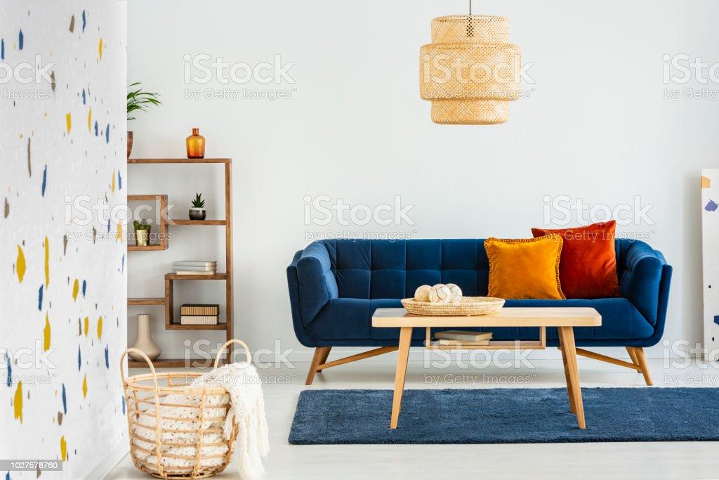 Lampe über holztisch vor blauen sofa mit kissen im modernen