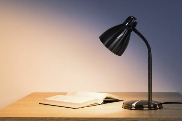Lamp and book on the desk top, space for text stock photo
